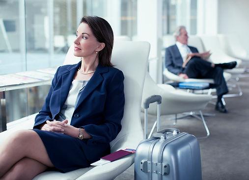 Бизнесмен с чемоданом ожидания в аэропор