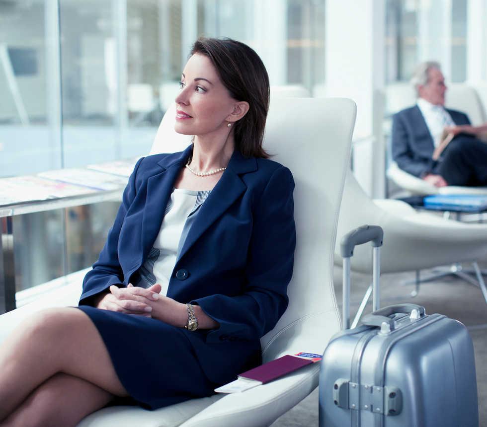 Geschäftsfrau mit Koffer im Flughafen wa