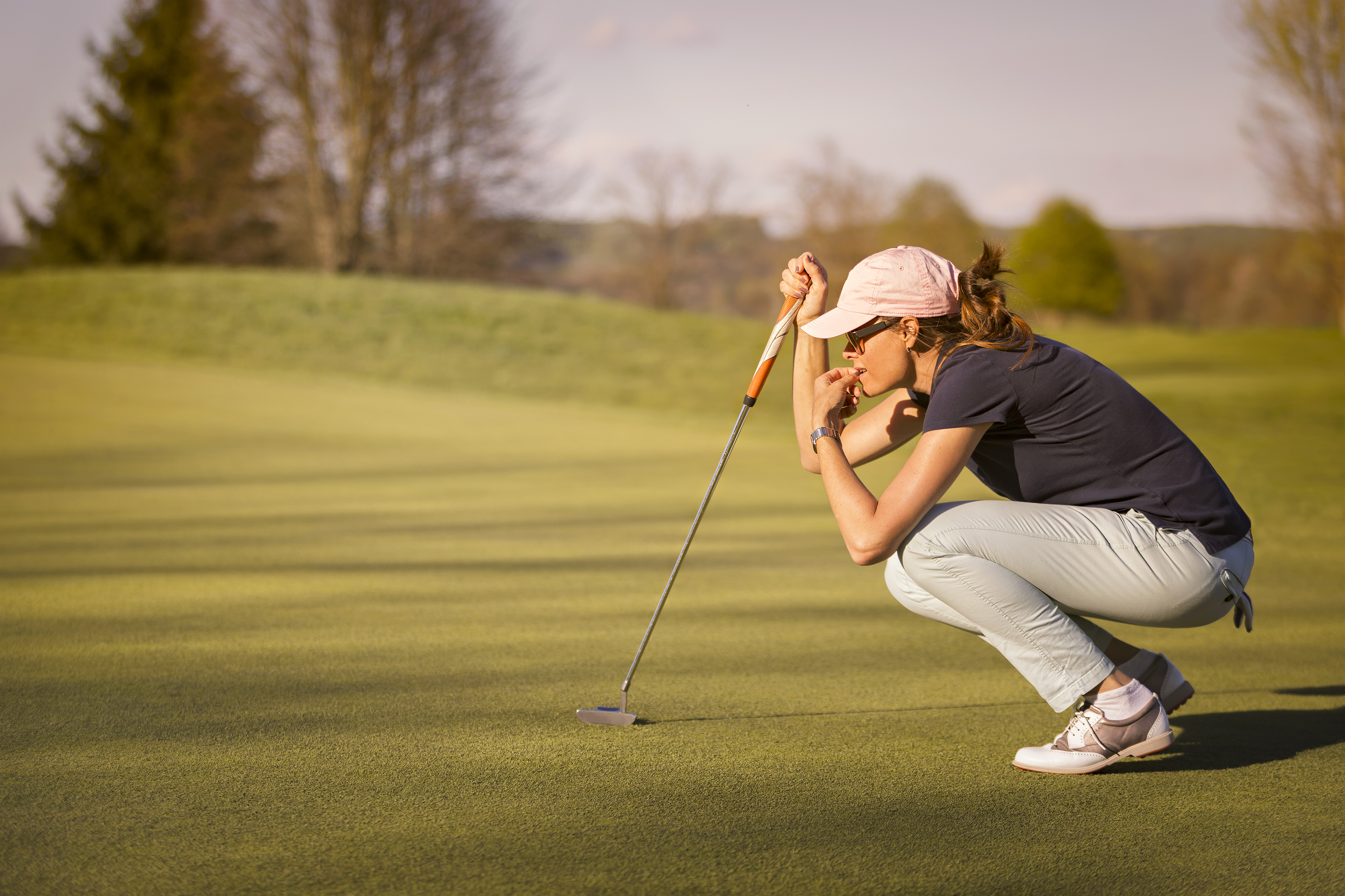 Woman golf player crouching and study the green before putting shot..jpg