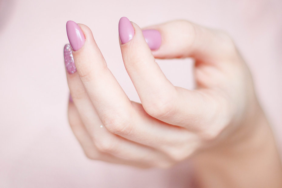 person-s-hand-with-pink-manicure-939835.