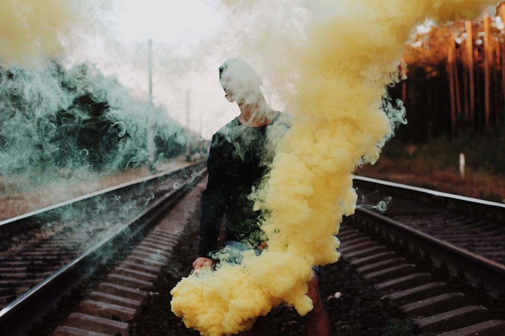 Homem em um trilho acende sinalizador amarelo, a fumaça tapa seu rosto