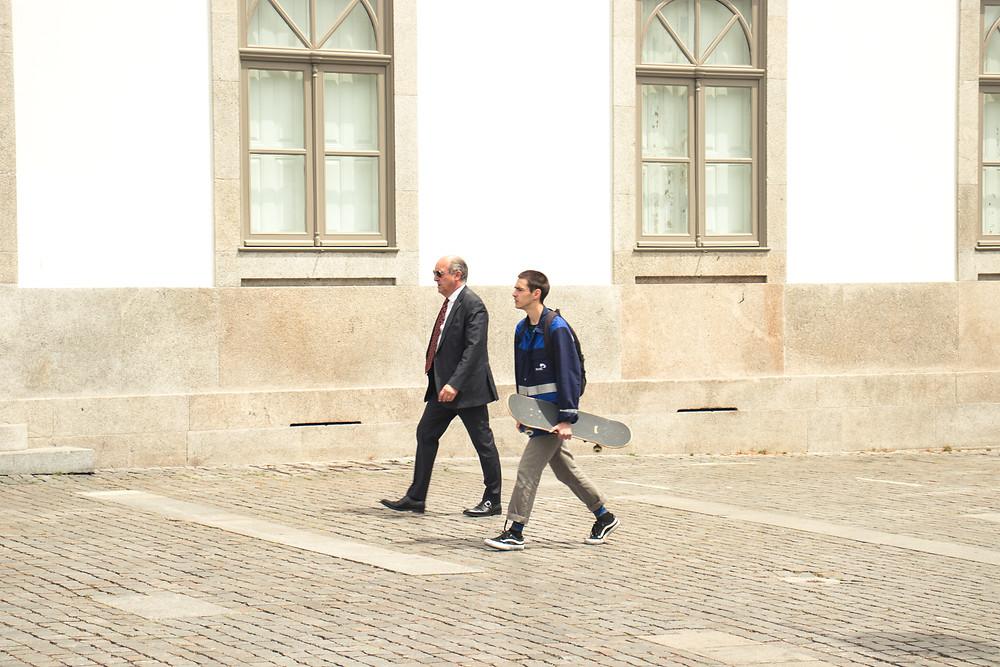 Senhor de aproximadamente 60 anos veste terno e anda ao lado de seu filho que segura o skate