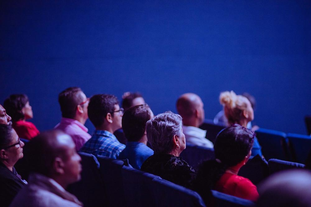 Pessoas sentadas em um auditório assistindo a uma palestra