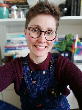 Me (white person with short hair and glasses) wearing space dungarees sitting in front of a bookcase.