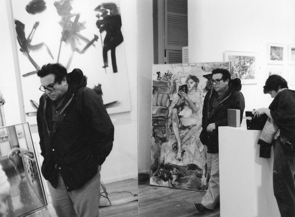 Black and white photo. Allan Stone standing in his gallery surrounded by paintings