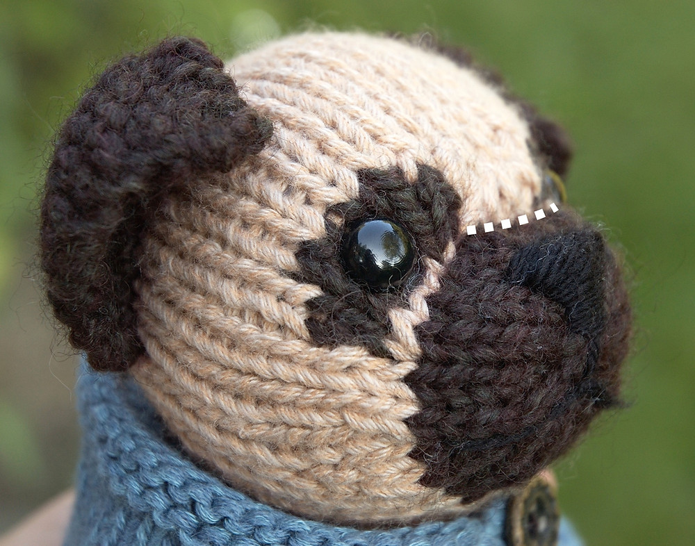 A knitted pug dog toy, shown in partial profile.