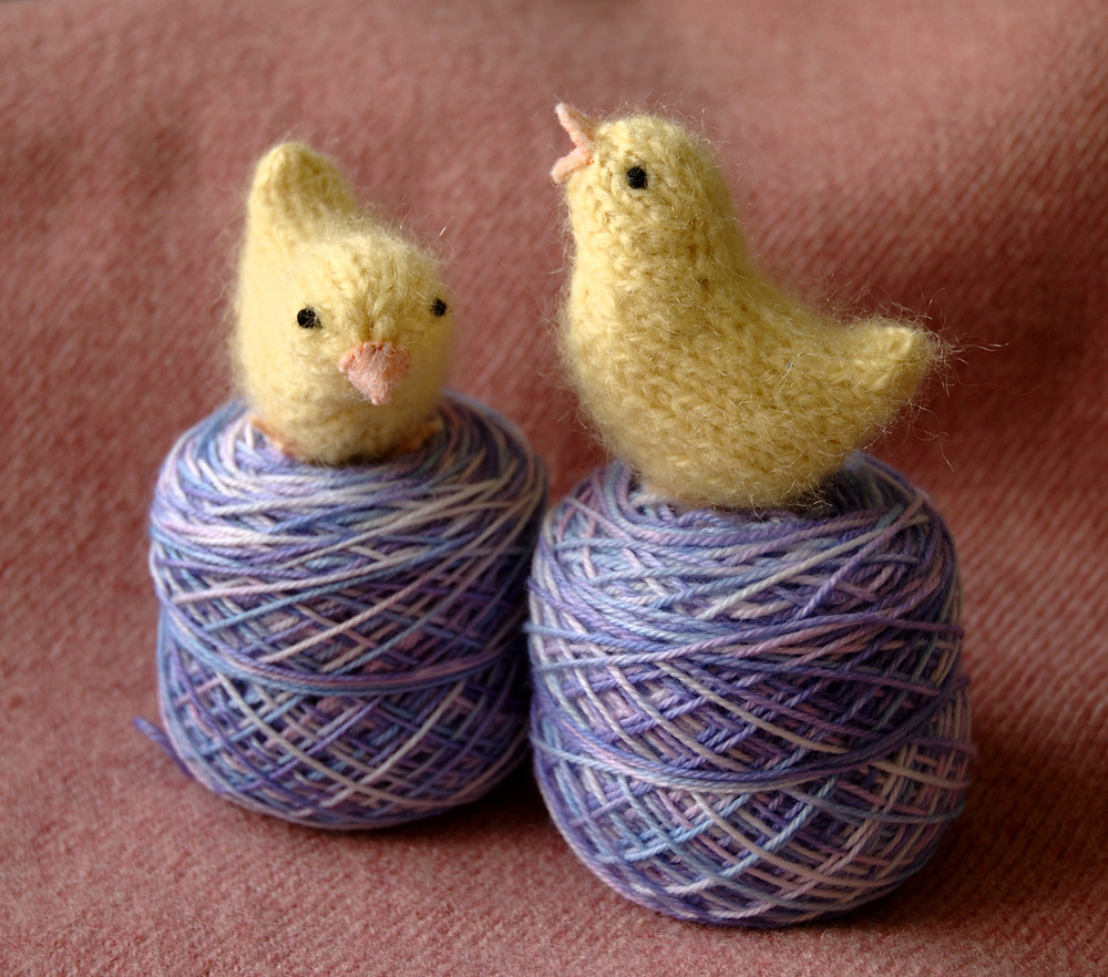 Shows two spring chick toys, sitting on top of balls of purple yarn