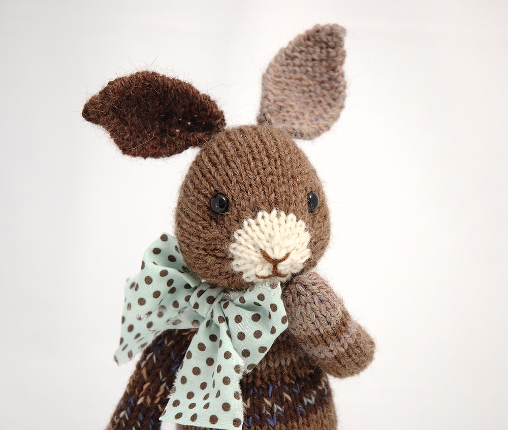 image of a brown knitted rabbit, with a polka-dotted fabric bow