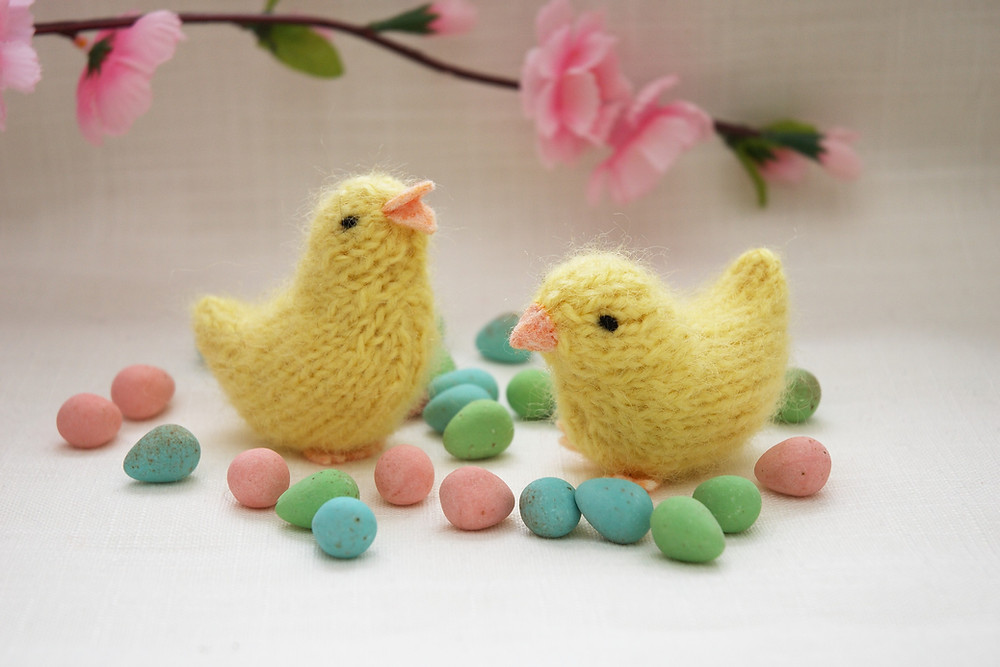 Shows two knitted chick toys, surrounded by colourful candy eggs