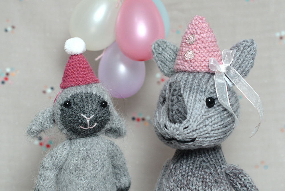 Two soft toys wearing party hats.