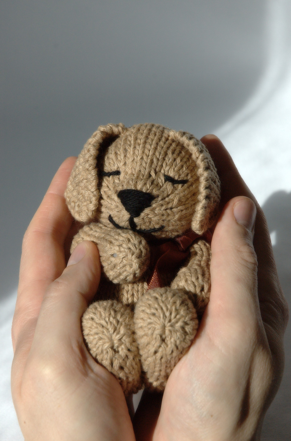 Close-up of adult hands holding the knitted toy puppy