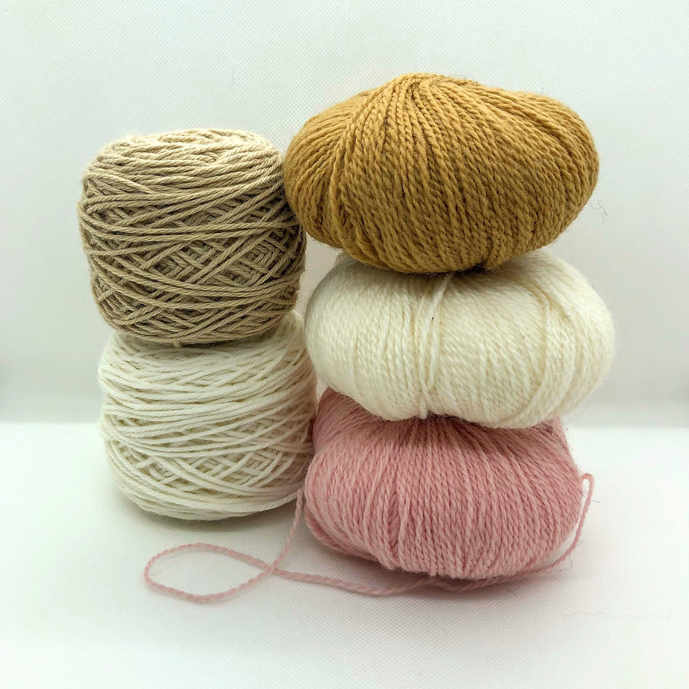 two stacks of yarn balls, in colours of light brown, white, and pink
