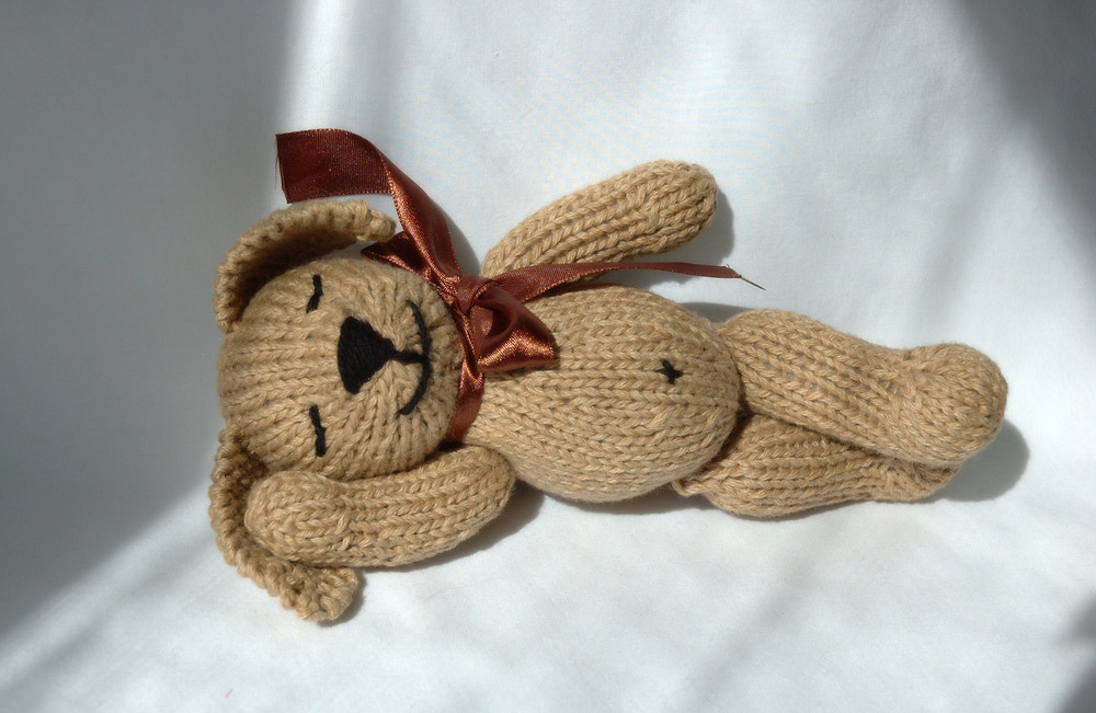 a knitted toy puppy in light brown yarn, with a brown ribbon