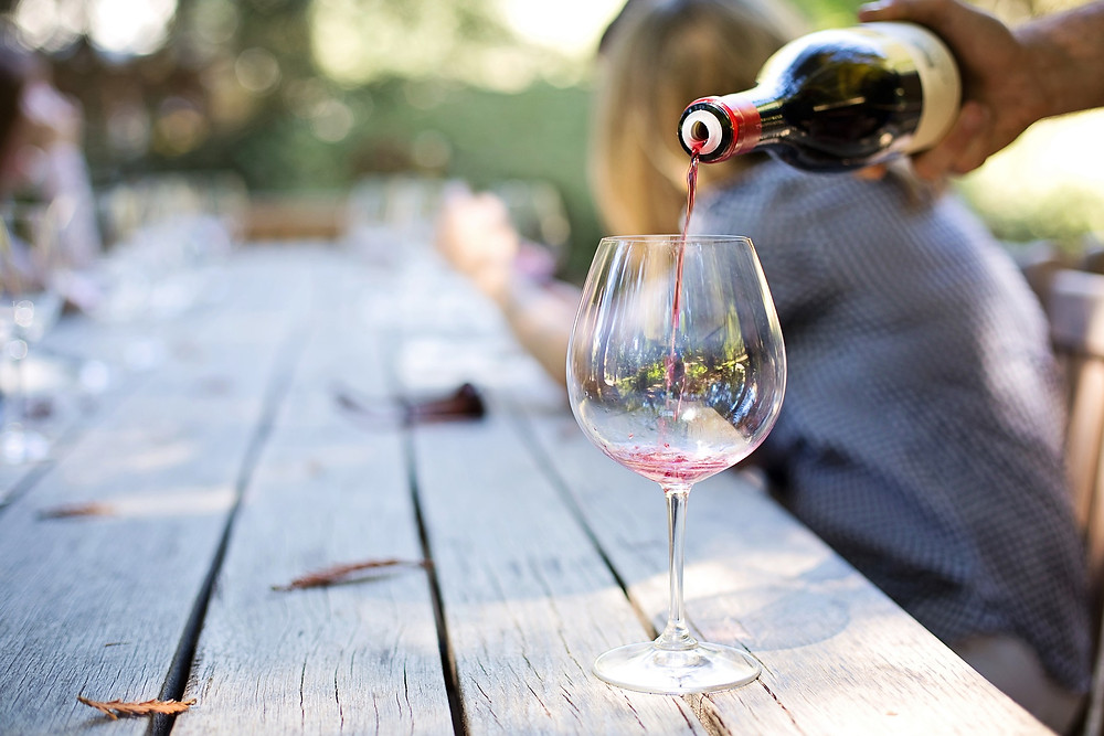 A man pours a glass of red wine on a wooden picnic table. A woman sits in the background.