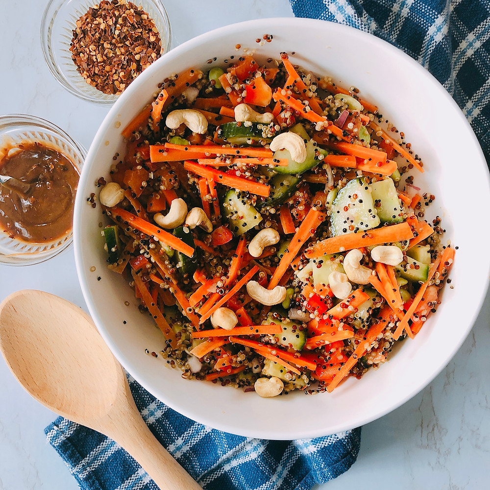 A big bowl of quinoa salad and peanut sauce sits on a blue and white checker tea towel on a marble counter top. To the bottom right of the salad is a large wooden spoon, and in the top right corner are two small dishes: one with peanut sauce and one with crushed red chilli flakes.