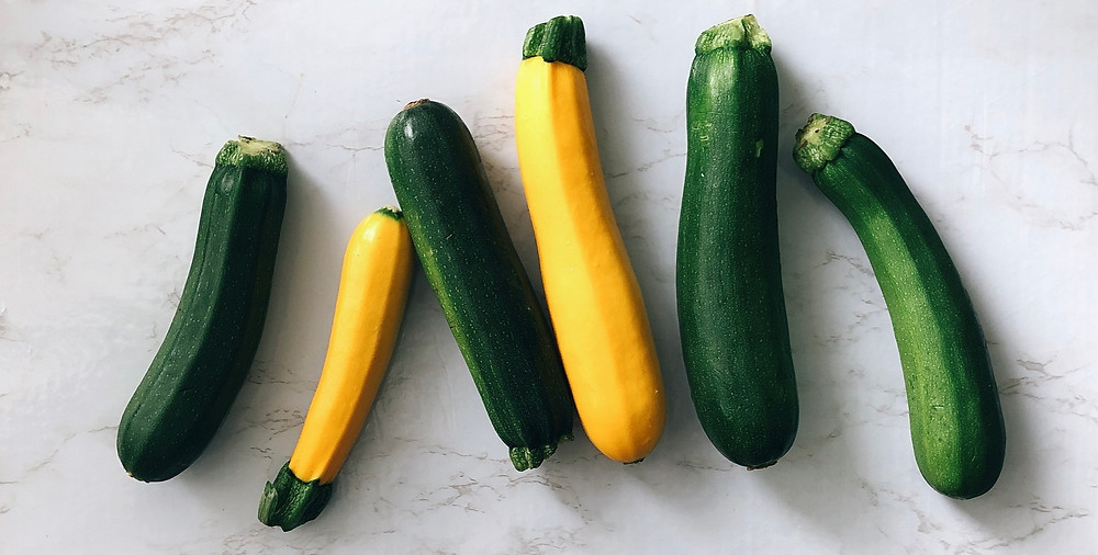 Six green and yellow zucchinis lay on a marble countertop.