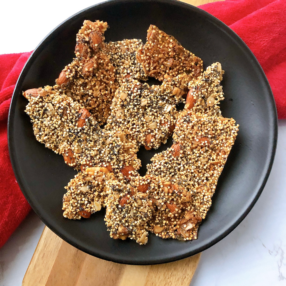 Broken pieces of quinoa brittle are displayed on a black plate that sits on a red towel and wooden board. The background is a marble countertop.