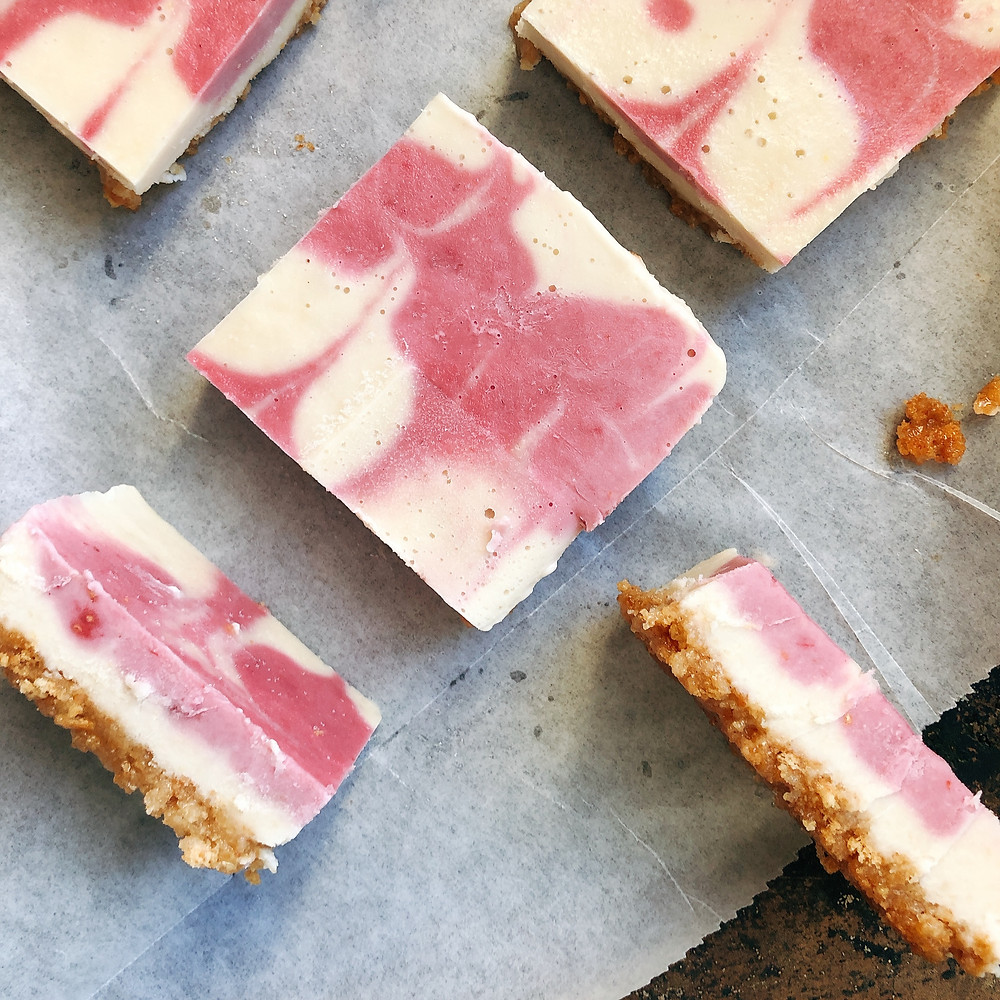 Raspberry Lemon Cashew Cheesecake Squares lay on parchment paper on a rustic looking tray.