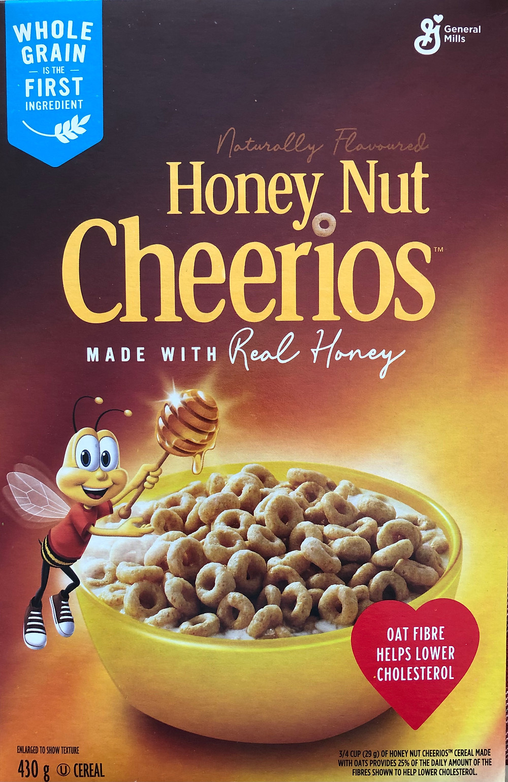 """The front-of-package Honey Nut Cheerios is displayed. In the top left corner in a blue banner, the box of cereal claims that """"Whole Grain is the First Ingredient"""". The box also states that it is naturally flavoured and made with real honey. In the bottom right corner, the box displays a heart with the statement """"Oat fibre helps lower cholesterol""""."""