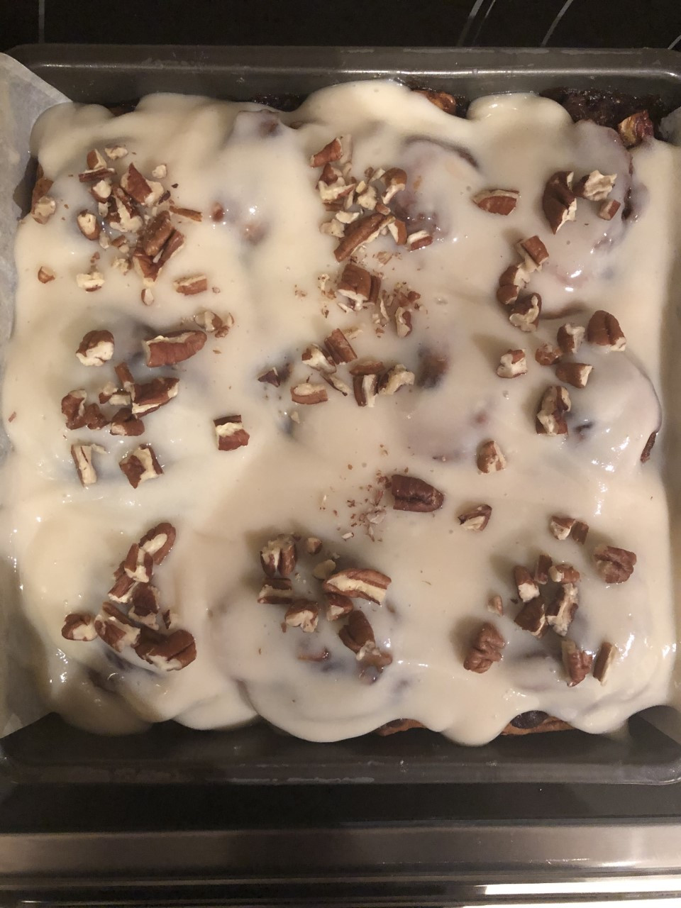 Baked cinnamon rolls with cream cheese frosting and chopped walnuts and pecans sit in their eight by eight square pan.