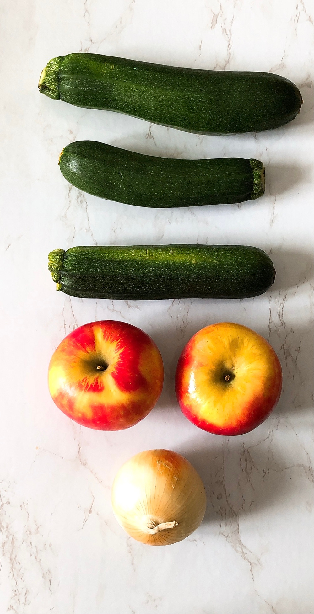 Three green zucchinis, two Honeycrisp apples, and a yellow onion lay on a marble countertop.