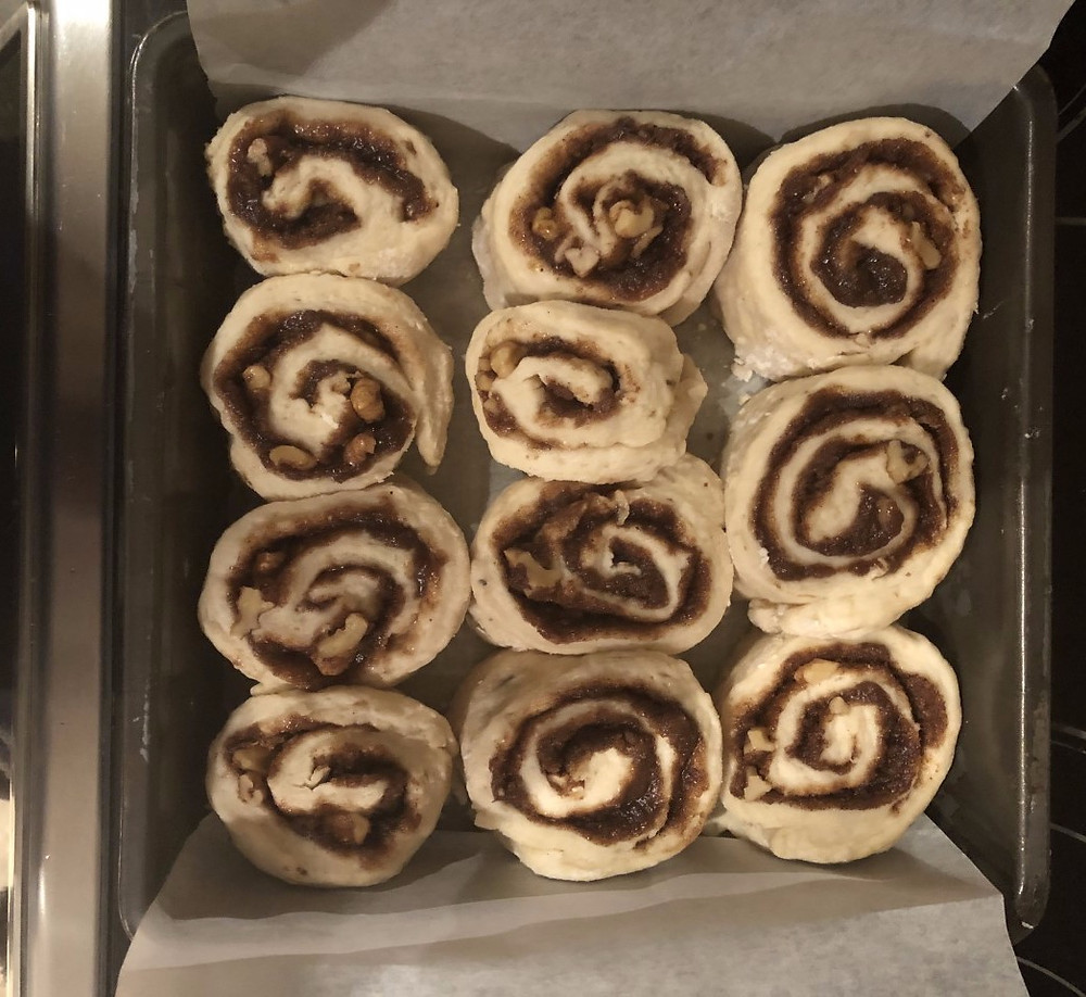Eleven raw cinnamon rolls sit in a eight by eight square pan before being baked. The pan is lined with parchment paper.
