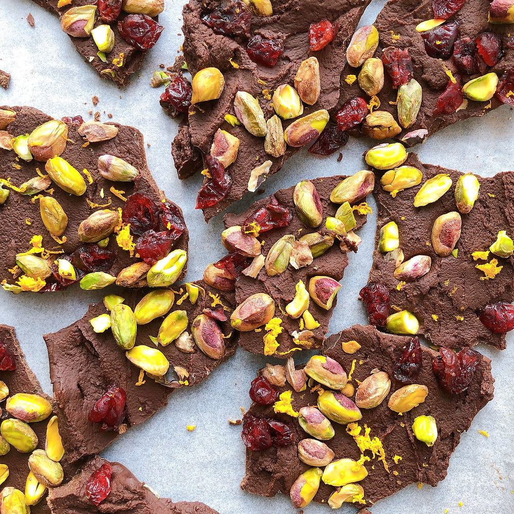 Chocolate bark topped with crushed pistachios, dried cranberries, and orange zest are broken into small pieces and lay on parchment paper.