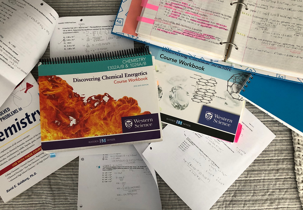 Chemistry textbooks, notes, and tests lay on a grey bedding