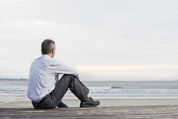 Thoughtful businessman sitting on a beac