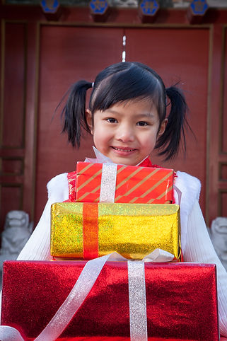 girl-holding-gifts-dressed-in-holiday-at