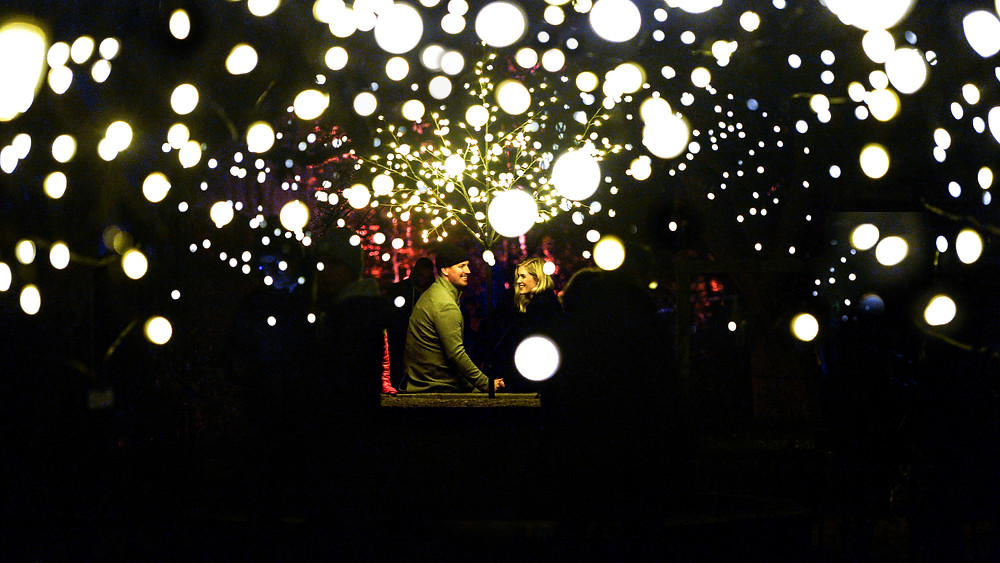 A man and a woman sitting under a tree in the dark and surrounded by circles of lights.