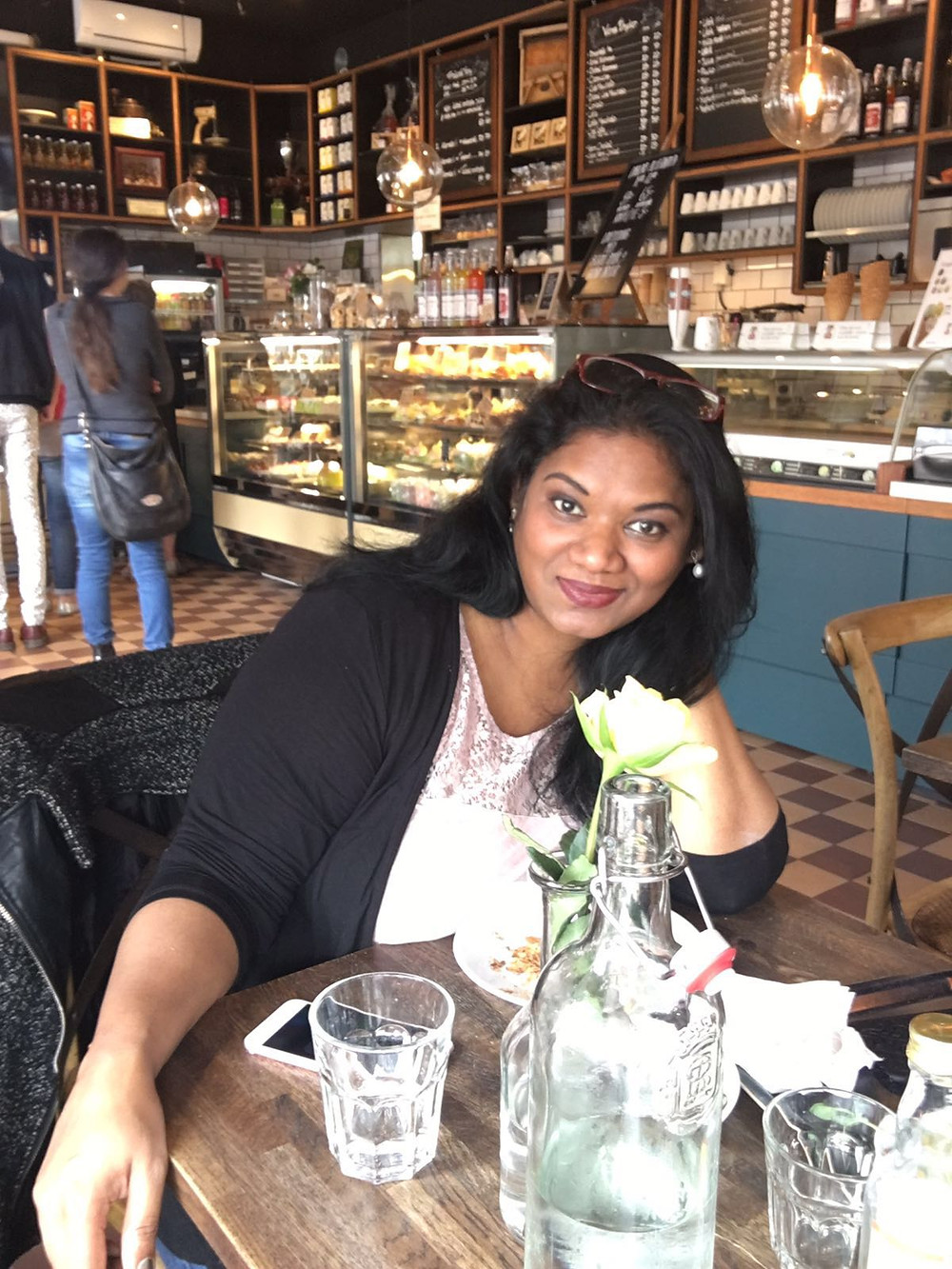 Photo of a woman sitting in a cafe looking into the camera and smiling.