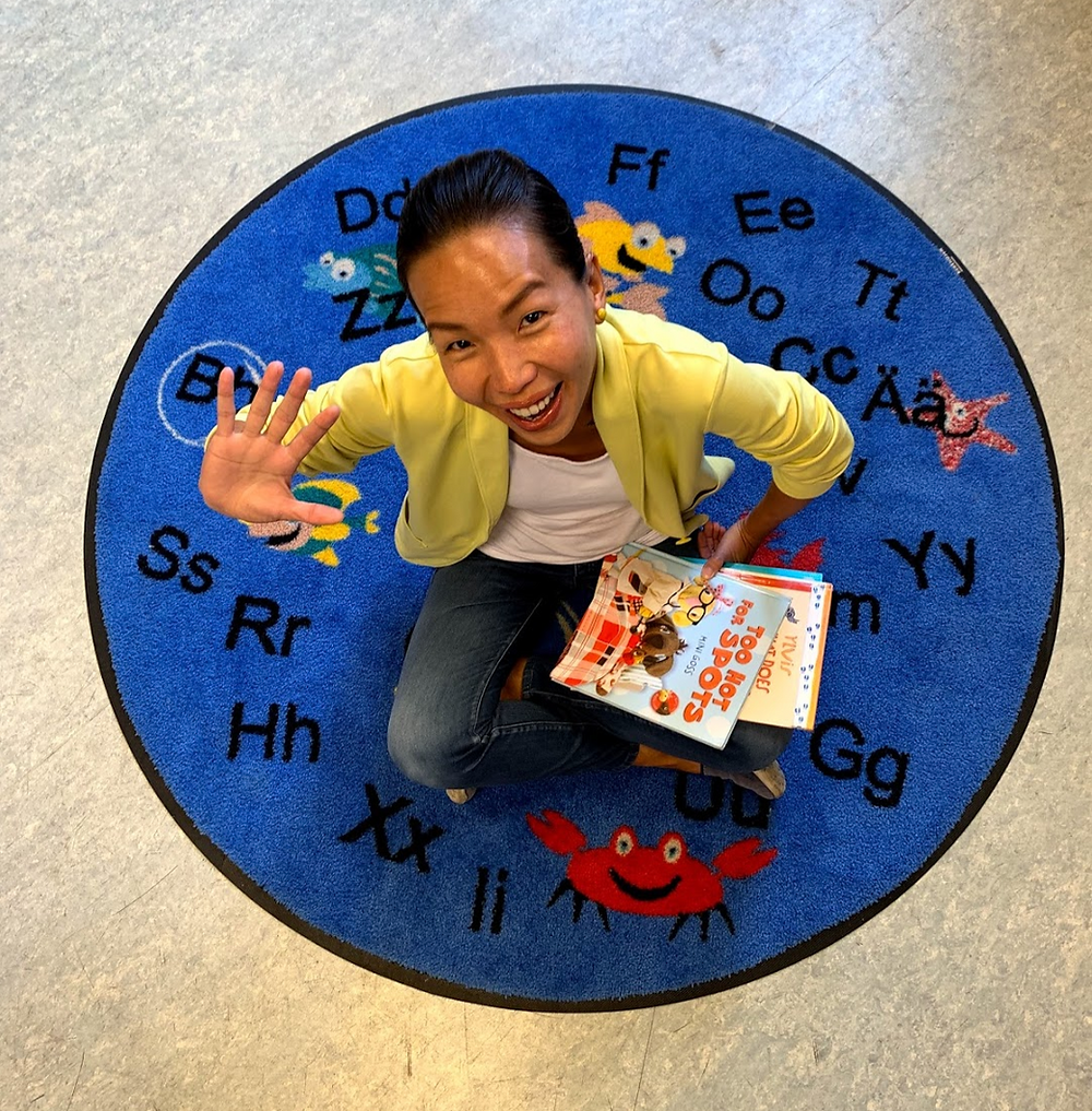 Tracy Tang is sitting on a circular carpet which has letters of the alphabet written all over. She is smiling and looking directly at the camera upwards with books in one hand and waving with the other.