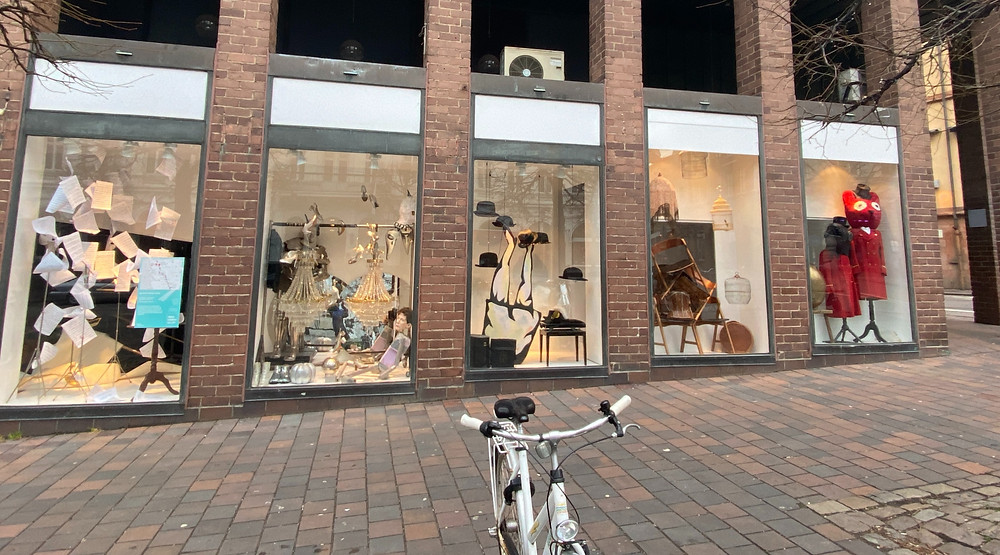 Four store windows featuring art installations. A bicycle in front of the picture.