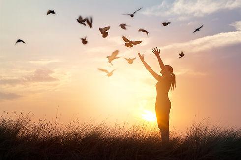 woman-praying-free-birds-nature-sunset-b