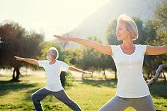Yoga at park. Senior family couple exerc