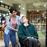 Man in wheelchair being assisted by his Personal Support Staff