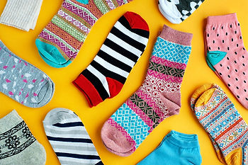 Several different designs of socks spread out across a surface.