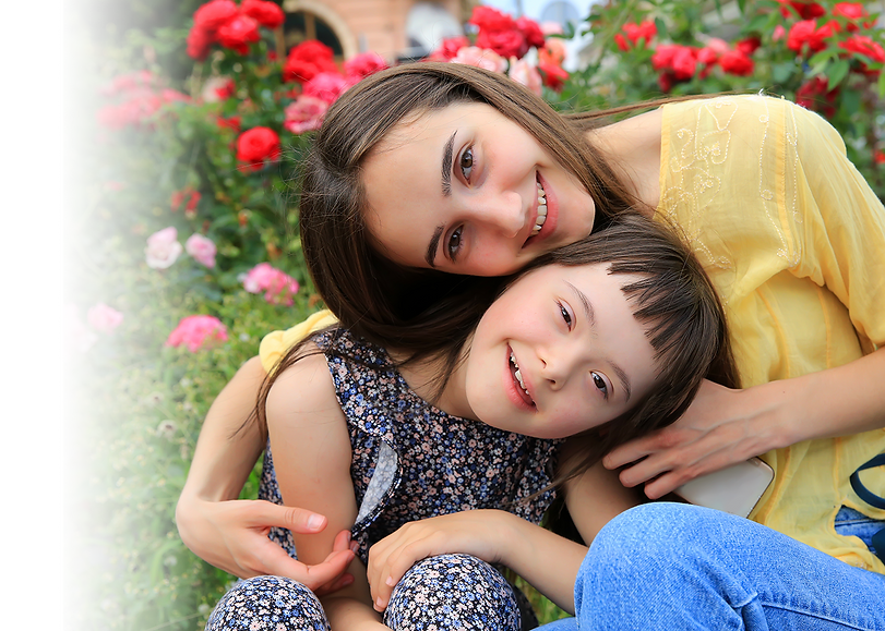 Young girl and her sister among pink and red flowers