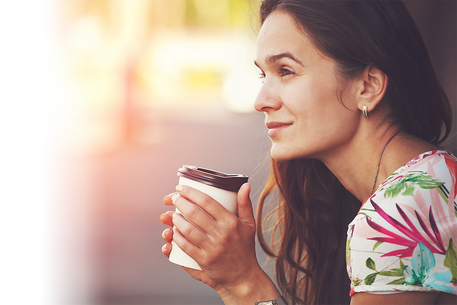 Peaceful woman with a cup of coffee in her hands