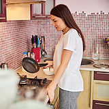 Homemaker staff cleaning a frying pan after preparing a meal