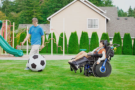 Child in a wheelchair playing soccer with his PCA/DSP