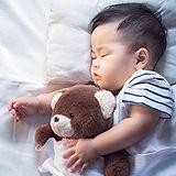 Sleeping baby with arm around a teddy bear