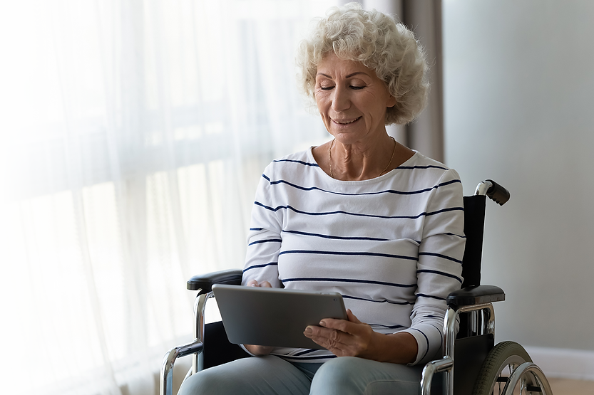 smiling elderly woman in wheelchair completing online contact us form