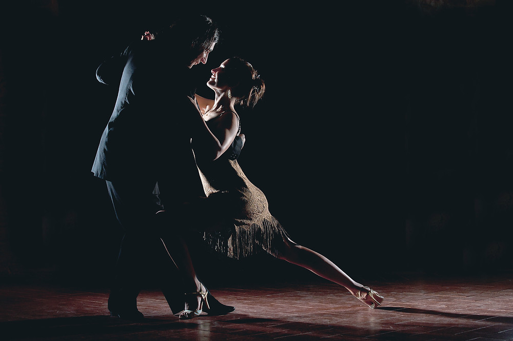 Man & woman doing a Latin-style dance in a ballroom in a spotlight.