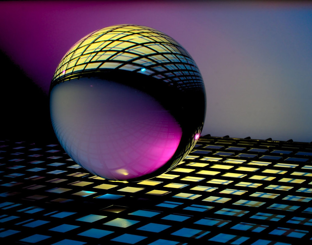 A CGI rendering of a metallic sphere hovering above a gridded floor.