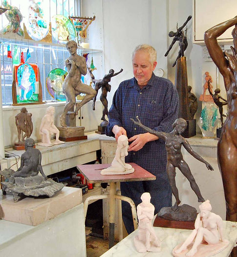 Artist David Klass in his studio with some of his figuarative sculpture