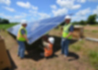 Picture of workers in hard-hats and safety vests installing solar panels in a field