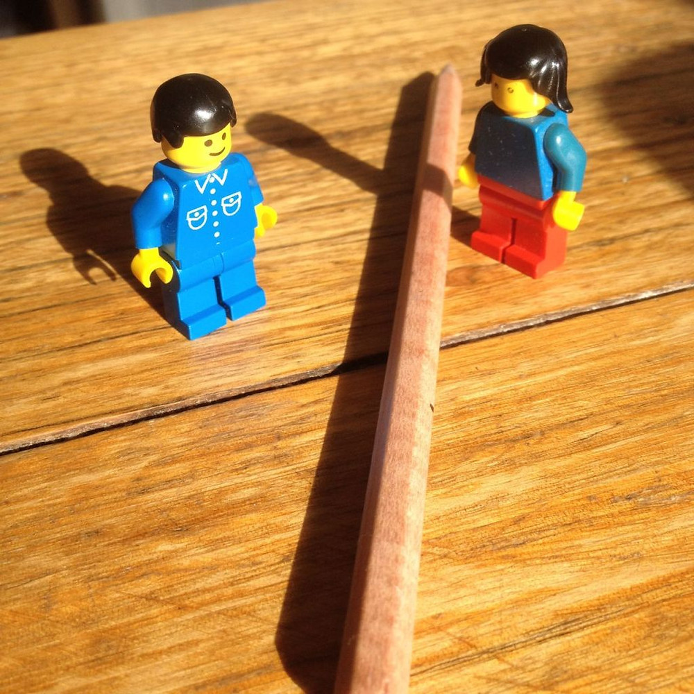 Lego men on a table with a pencil
