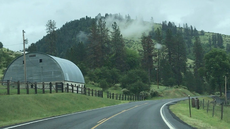 Round topped barn in Idaho with misty mountains, photo by Ray Monde